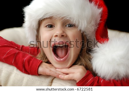 A beautiful young girl wearing a santa hat excited about christmas