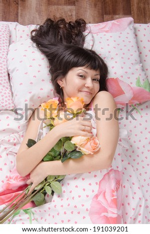 A beautiful young girl who lies in bed, gave flowers