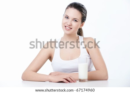 A beautiful young girl with a glass of milk on a white background - stock photo