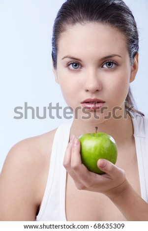 A beautiful young girl with an apple on a white background - stock photo