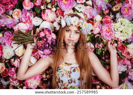 A beautiful young girl with flowers bouquet near a floral wall. - stock photo
