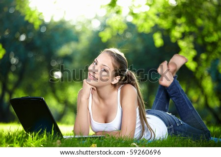 A beautiful young girl with laptop in the park - stock photo