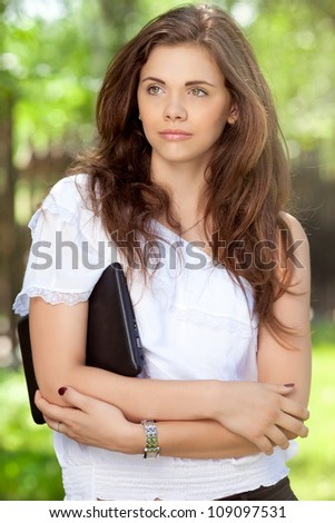 A beautiful young girl with laptop outdoors - stock photo