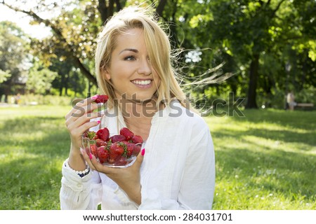 A beautiful young girl with strawberries on the grass - stock photo