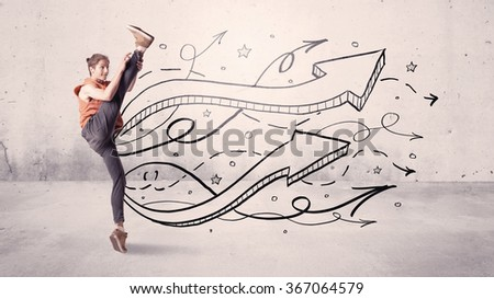 A beautiful young hip hop dancer dancing contemporary street dance in front of urban grey wall background with lines and arrows concept - stock photo