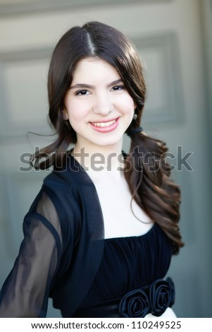 A beautiful young hispanic woman in a black dress smiles at the camera. - stock photo
