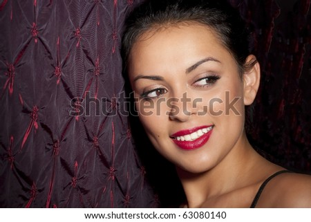 a beautiful young hispanic woman leaning against a wall. - stock photo