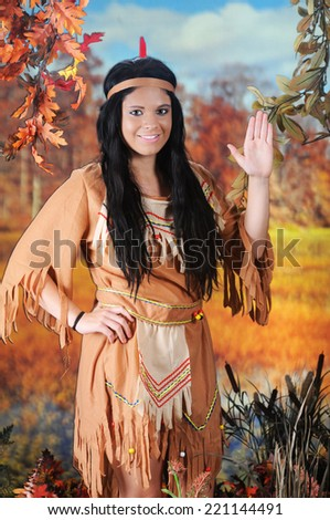 A beautiful young Indian teen giving her greeting on the banks of a colorful fall swamp. - stock photo