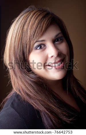 A beautiful young Latin woman with a smile on her face and highlighted hair. - stock photo