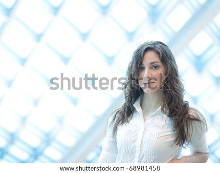 A beautiful young librarian with modern building in background - stock photo