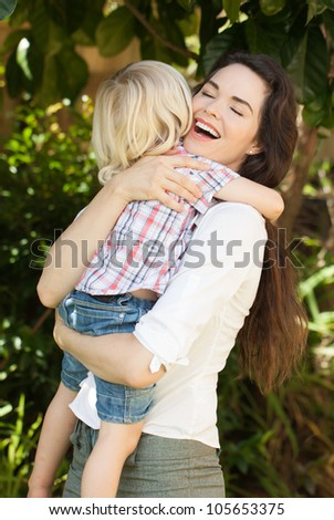 A beautiful young loving mother smiling and hugging her young child. - stock photo