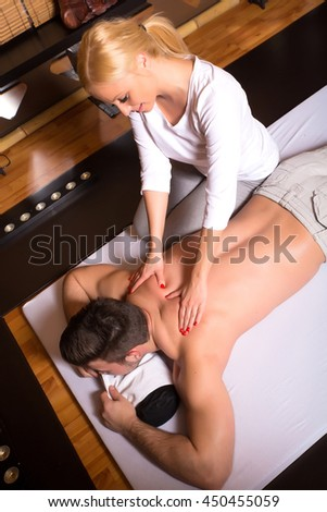 A beautiful young masseuse applying a massage to a male client in a studio.