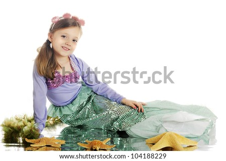 A beautiful young mermaid with a watery reflection among starfish and seaweed.  On a white background. - stock photo