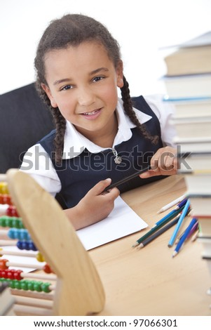 A beautiful young mixed race African American girl writing or drawing in a school classroom surrounded by books and an abacus - stock photo