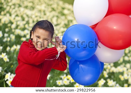 A beautiful young mixed race girl playing with balloons in a field of daffodils