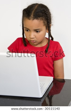 A beautiful young mixed race girl surfing the wold wide web on a white laptop computer
