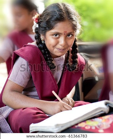 A beautiful young mixed race girl writing in a school classroom surrounded by book - stock photo
