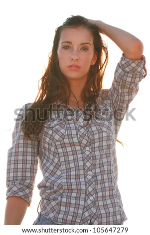 A beautiful young model in a western themed outfit poses in the desert - stock photo