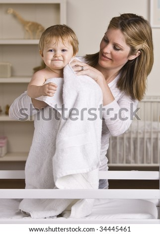 A beautiful young mother drying off her baby with a towel.  They have slight smiles on their faces.  Vertically framed shot. - stock photo