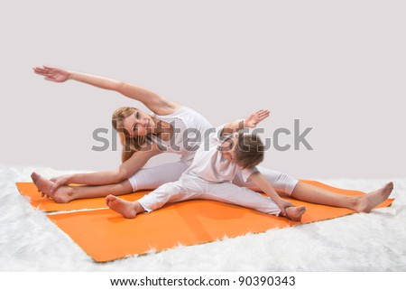 A beautiful young mother practices yoga with her son - stock photo