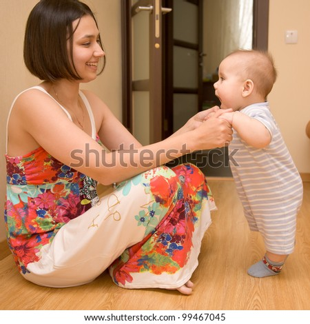 A beautiful young mother wearing a dress with flowers and a charming kid on the floor. Baby learning to stand - stock photo