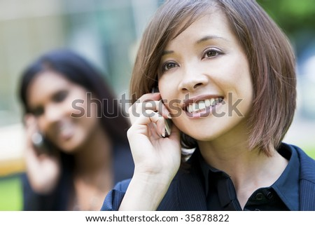 A beautiful young oriental woman with a wonderful smile chatting on her cell phone with Indian Asian woman on her phone out of focus behind her.