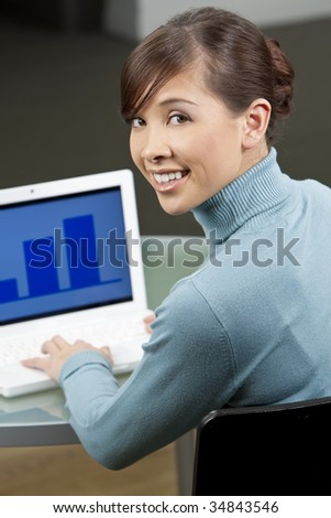A beautiful young oriental woman with a wonderful toothy smile using a laptop in her office - stock photo