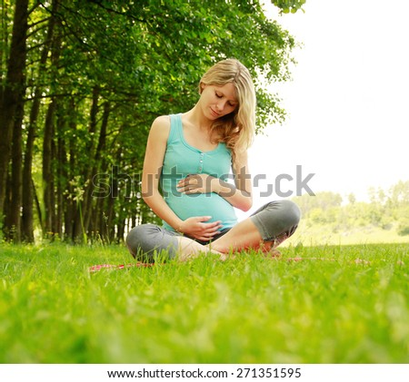 a beautiful young pregnant girl on the nature  - stock photo