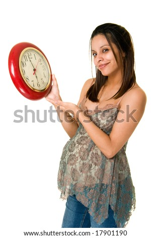 A beautiful young pregnant Hispanic woman looking at a clock and waiting anxiously for the birth of her baby. Isolated on white background. - stock photo