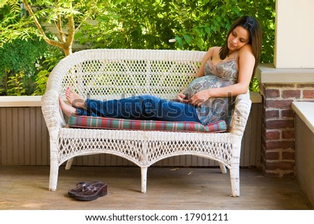A beautiful young pregnant Hispanic woman relaxing outside white waiting for the birth of her baby. - stock photo