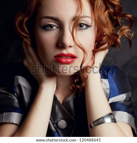a beautiful young red-haired model in an arty jacket with metal wristband holding her head over black background. close-up. studio shot - stock photo