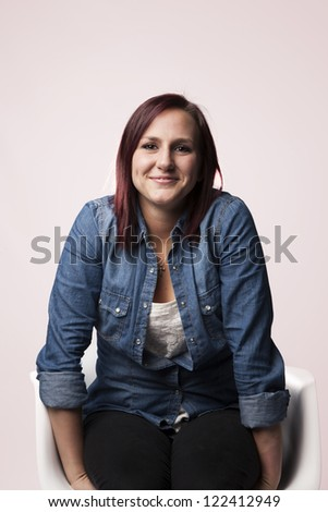 A beautiful young redhead woman casually sits in a chair and smiles. - stock photo