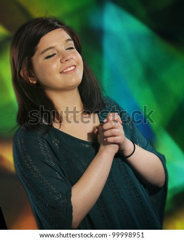 A beautiful young teen happily praying with stained glass in the background. - stock photo