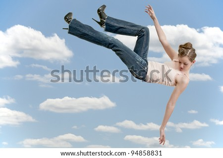 A beautiful young teenage woman falling through the sky - stock photo