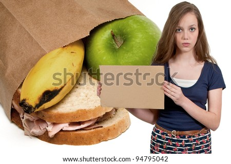 A beautiful young teenager woman holding up a blank sign buy a bag lunch - stock photo