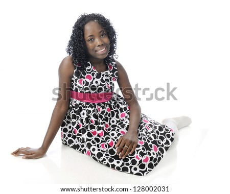 A beautiful young tween happily sitting on the ground in her sundress. On a a white background. - stock photo
