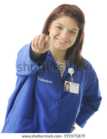 A beautiful young volunteer happily pointing at the viewer, inviting him/her to volunteer too.  Focus on girl's eyes.  On a white background. - stock photo