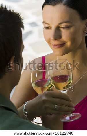 A beautiful young woman and her boyfriend toasting with glasses of white wine while bathed in summer sunshine - stock photo
