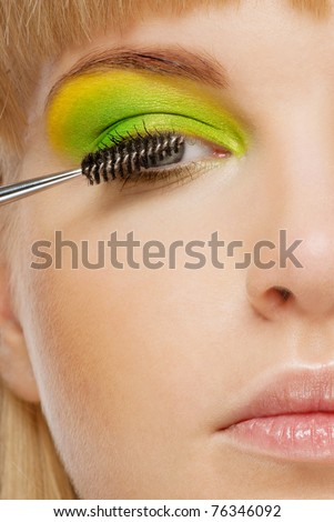 A beautiful young woman applying mascara ush closeup, isolated on a white background - stock photo