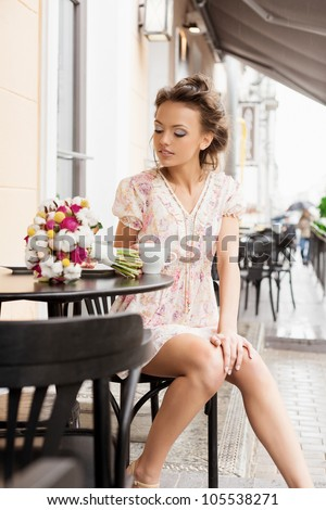 A beautiful young woman are drinking tea. Outdoors - stock photo