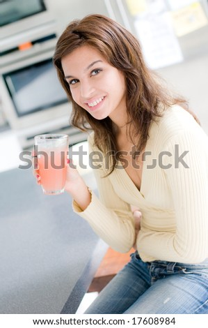 A beautiful young woman drinking grapefruit juice