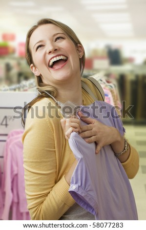 A beautiful young woman excitedly picks out a blouse while shopping.  Vertical shot.