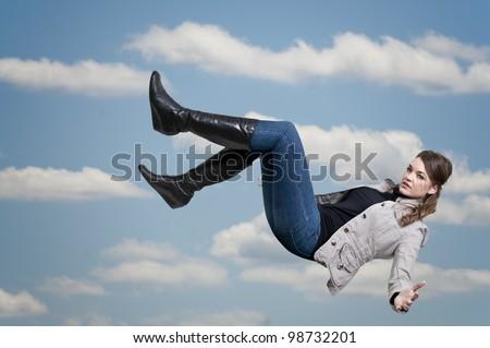 A beautiful young woman falling through the sky - stock photo