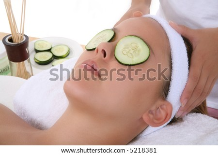 A beautiful young woman getting a facial at the spa - stock photo