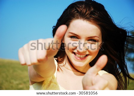 A beautiful young woman giving you a thumbs up and smiling in a field with a blue sky.