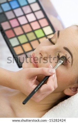 A beautiful young woman having the final touches applied to her make up by a beautician - stock photo
