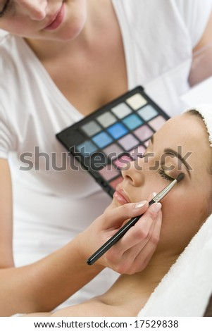A beautiful young woman having the finishing touches applied to her make up by a beautician - stock photo