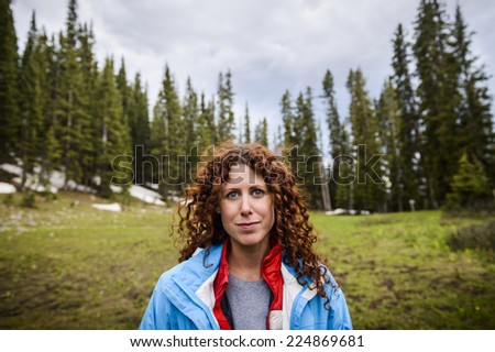 a beautiful young woman hiking in the mountains - stock photo