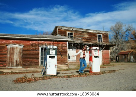 A beautiful young woman hitch hiking from a deserted gas station - stock photo
