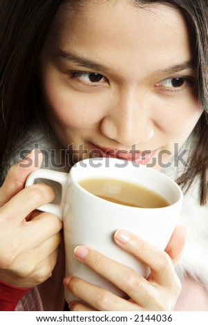 A beautiful young woman holding a cup of hot drink - stock photo